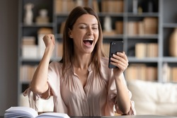 Close up overjoyed woman looking at phone screen, celebrating success, showing yes gesture, sitting at work desk, young female excited by good news in email or message, job promotion, money refund