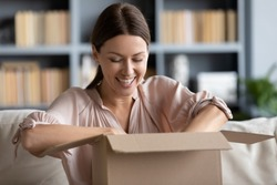 Close up overjoyed young woman unpacking cardboard box at home, satisfied customer received awaited parcel with online store order, sitting on couch, good quick delivery service concept