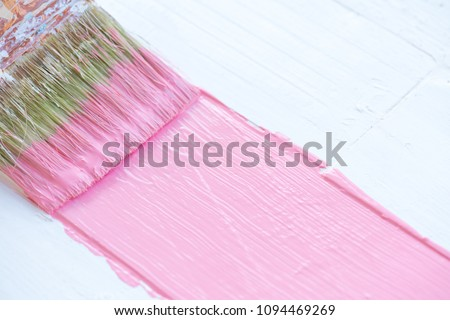 Close up paintbrush painting pink color on a white wooden table