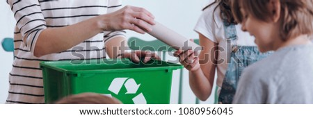 Close-up panorama of a school girl handing a paper tube to a teacher with a recycling bin during environment class for Earth Day