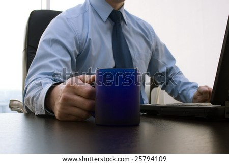 Close up part of manager for the working on computer in office and tea in blue cup