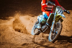 Close-up part of mountain bikes race in dirt track in sunshine day time. Concept focus of during an acceleration in action sport
