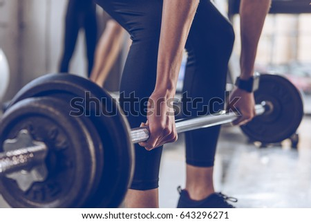 Close-up partial view of sportswoman lifting barbell at gym workout #643296271