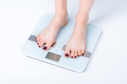 Close-up partial view of young woman standing on digital scales