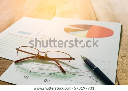 Close up pen with summary report and eyeglasses on table office. Concept of Data Analysis, Investment Planning, Business Analytics.