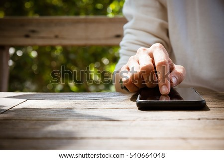 Close up people hand using smartphone on the wooden table in the park stock photo