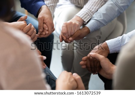 Close up people sit in circle holding hands participating at group therapy session. Receiving sharing psychological support, go through addiction together, help each other overcome dependence concept