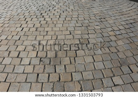 Close up perspective view of a sidewalk made of cobblestones. Pattern of grey brown blocks. Abstract picture surface with curving lines.  #1331503793