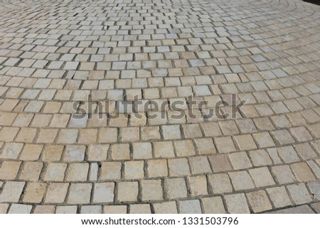 Close up perspective view of a sidewalk made of cobblestones. Pattern of grey brown blocks. Abstract picture surface with curving lines.  #1331503796