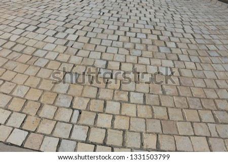 Close up perspective view of a sidewalk made of cobblestones. Pattern of grey brown blocks. Abstract picture surface with curving lines.  #1331503799
