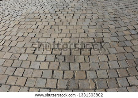 Close up perspective view of a sidewalk made of cobblestones. Pattern of grey brown blocks. Abstract picture surface with curving lines.  #1331503802