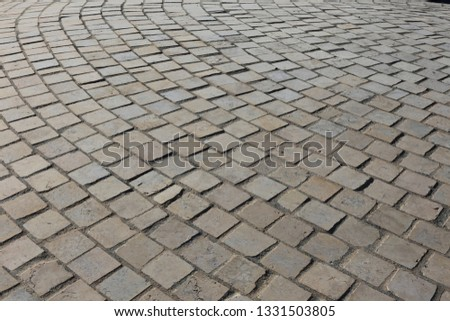 Close up perspective view of a sidewalk made of cobblestones. Pattern of grey brown blocks. Abstract picture surface with curving lines.  #1331503805