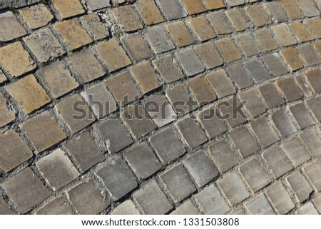 Close up perspective view of a sidewalk made of cobblestones. Pattern of grey brown blocks. Abstract picture surface with curving lines.  #1331503808
