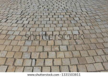 Close up perspective view of a sidewalk made of cobblestones. Pattern of grey brown blocks. Abstract picture surface with curving lines.  #1331503811