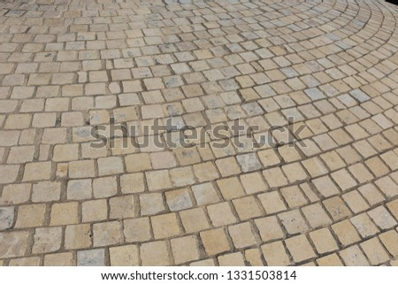 Close up perspective view of a sidewalk made of cobblestones. Pattern of grey brown blocks. Abstract picture surface with curving lines.  #1331503814