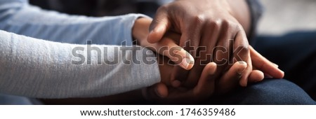 Close up photo african couple in love, woman man holding hands. Gesture of sincere feelings, compassion, apology, reliable friend, share pain or happiness. Horizontal banner for website header design Stock photo ©