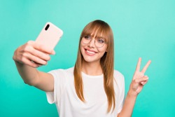 Close up photo amazing beautiful she her lady arm hand hold telephone make take selfies v-sign symbol positive friendly speak tell skype wear specs casual white t-shirt isolated teal green background