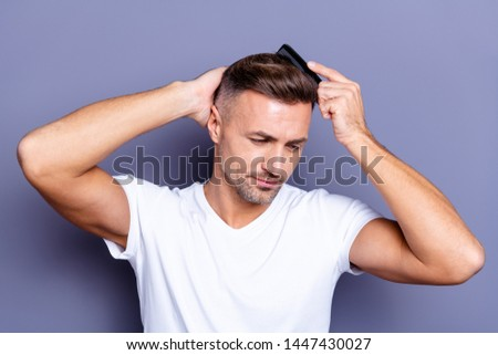 Close up photo amazing he him his middle age thought thoughtful macho hands arms plastic hair styling brush take care hairdo after barber shop visit wear casual white t-shirt isolated grey background