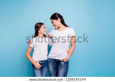 Close up photo amazing pretty two people brown haired mum small little daughter stand close hugging lovely look eyes rejoice wearing white t-shirts isolated on bright blue background #1308185194