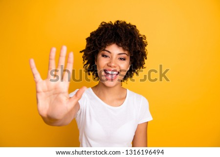 Close up photo beautiful amazed she her dark skin lady glad arms hands five fingers raised show countable uncountable things lesson wearing casual white t-shirt isolated yellow bright background Foto d'archivio ©