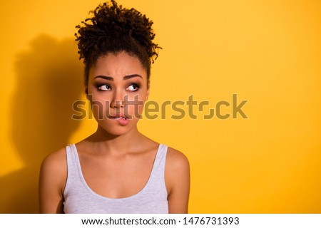 Close up photo beautiful amazing she her dark skin lady look not smiling empty space oops I did it again facial expression bite lip feel guilty wear casual tank-top isolated vivid yellow background