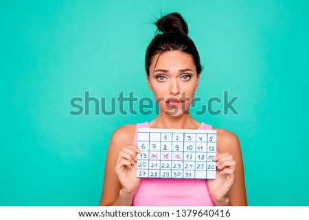 Close up photo beautiful amazing she her lady funny hairdo bite lips mouth hold hand arm paper calendar inconvenient situation oops wear casual pink tank-top isolated teal turquoise background