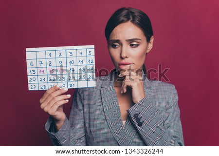 Close up photo beautiful doubtful business she her lady hand chin bite lip watch see look calendar period pause stop late wearing formal-wear checkered plaid suit isolated dark red vivid background