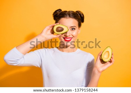 Close up photo beautiful she her lady pretty hairdo hold slices avocado hide eye used amazing salon mask oil extract procedure wearing casual white pullover clothes isolated yellow background