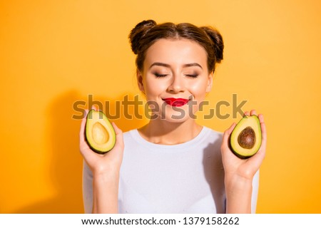 Close up photo beautiful she her lady pretty hairdo hold two half slices avocado eyes closed amazing salon procedure cool red color lipstick wear casual white pullover isolated yellow background