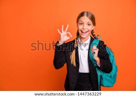 Close up photo beautiful she her little lady funny hairdo hand arm fingers raised okey symbol approval quality news wear formalwear shirt blazer skirt school form bag isolated bright orange background