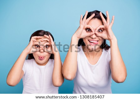 Close up photo beautiful two people brown haired mom little daughter friends look finger specs okey symbol tongue out mouth silly shapes figures wear white t-shirts isolated bright blue background