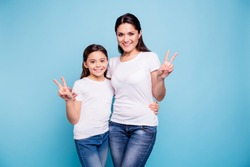 Close up photo beautiful two people brown haired mom little daughter showing v-sign hugging best friends look similar wearing white t-shirts isolated bright blue background