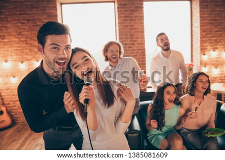 Close up photo best friends karaoke weekend vacation hang out sing duet lyric melody she her ladies he him his guys help sing words song wear dresses shirts formal wear sit sofa loft room indoors