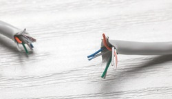 close up photo - broken internet link twisted pair cable on white wooden surface
