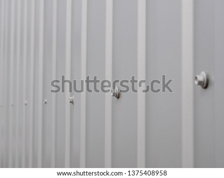 Close up photo. grooved metal surface texture, galvanized steel background with bolts
