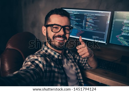 Close up photo handsome he him his guy coder make take selfies blog advising web agency thumb up development outsource IT processing language monitors table office wear specs formalwear plaid shirt