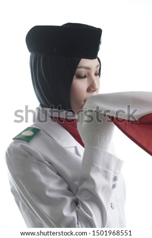Close up photo Indonesian National Flag Hoisting Troop kissing flag. National Paskibraka Council isolated in white