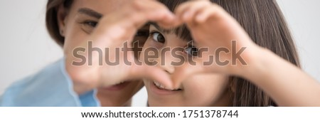 Close up photo little daughter and mother join fingers forming heart shape as concept sign of charity and donation, adoption kid and childcare, family bond. Horizontal banner for website header design