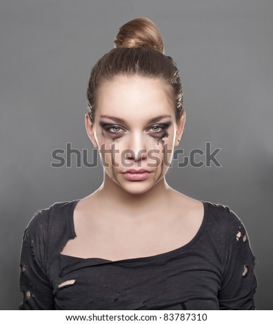 Close up photo of a beautiful girl crying, wearing torn clothes.