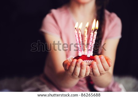Close-up photo of a cupcake with five lighted candles in child's hands, focus on a cupcake