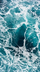 Close-up photo of a drone sea wave foam stains, incredible color of ocean clear water, beautiful natural background of sea water, aerial view