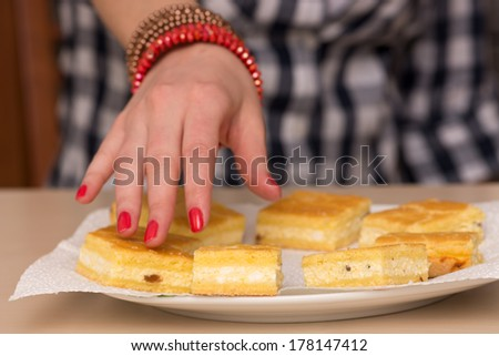 Close up photo of a female hand reaching out for a cake