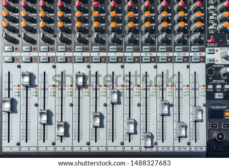Close up photo of a professional sound mixer with many adjustments, knob switches and buttons of audio mixer control panel.