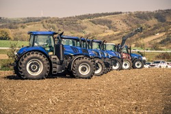 Close-up photo of a row of modern big tractors standing in the field during sunny autumn day. Tractor dealership event with presentation of front loader.