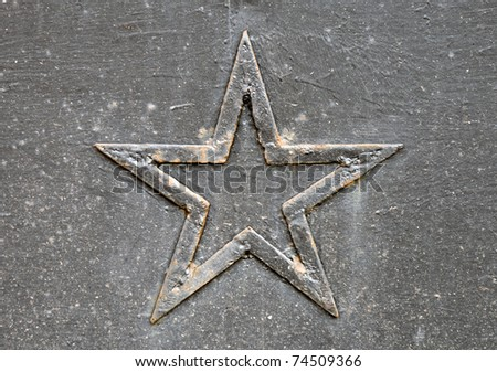 Close-up photo of a rusted five-point star on the metal wall