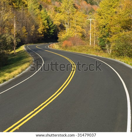 Close-up photo of a scenic highway winding through a colorful fall forest in Vermont