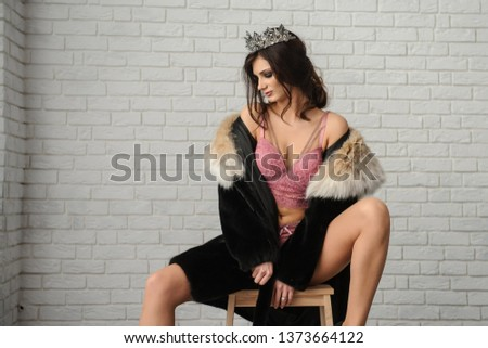close up photo of a sexy fashion woman in black fur coat with beige collar, in pink underwear with a crown on her head sitting on a chair on white brick background #1373664122