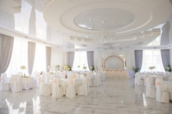 close up photo of a wedding banquet room: arranged white round tables with