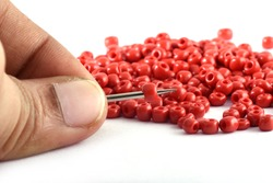 Close up photo of a woman's hand nailing beads on a needle.Beads with needle. macro,used in finishing fashion clothes. make bead necklace, beads for woman of fashion,Bead Crochet. Daily Beading.