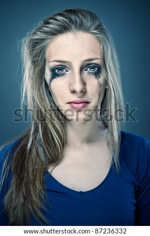 Close up photo of a young beautiful woman crying, with smudged make up